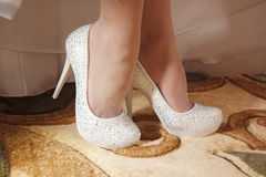 White wedding shoes on the feet of the bride Royalty Free Stock Photography