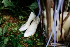 White wedding shoes on the grass. Next to a white candle Royalty Free Stock Photos