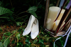 White wedding shoes on the grass. Next to a white candle Royalty Free Stock Images