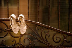 White wedding shoes hang. A wrought iron fence Royalty Free Stock Photo