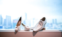 White wedding shoes. White male and female wedding shoes of the bride by a window Stock Photography