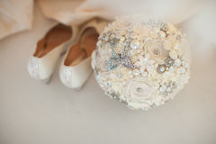 White wedding shoes and modern wedding bouquet Stock Images