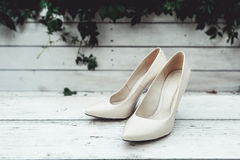 White wedding shoes in the rain on a white wooden table Stock Image
