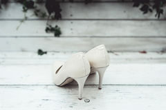 White wedding shoes in the rain on a white wooden table Stock Photography