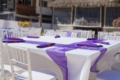 White wedding table decorated with purple bows on Stock Photos