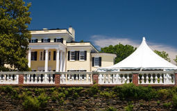 White wedding tent at mansion. Large white party tent set up on a front lawn of a large mansion for a wedding Stock Image