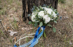 White wedding wedding bouquet with silk blue ribbons supported on the tree royalty free stock images