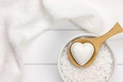 White wellness with bath salt, bath bomb and towel. On wooden surface stock photos