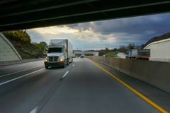 White 18 wheeler semi truck and overpass. Big rig 18 wheeler commercial vehicle semi truck on highway going under overpass Stock Photos