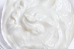 White whipped or sour cream on white background, close up. Macro stock image
