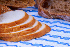 White and wholegrain bread on a blue tablecloth Royalty Free Stock Photos
