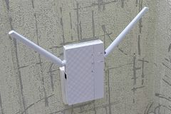 Wireless Router close-up. White Wi-Fi router with two antennas for high-speed wireless Internet. Installed on the wall of the room Stock Photos