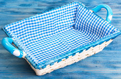 White wicker basket of bread with checkered cloth on blue backgr Royalty Free Stock Photo