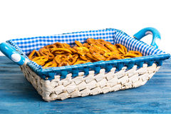 White wicker basket of bread with checkered cloth on blue backgr Stock Photo