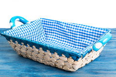 White wicker basket of bread with checkered cloth on blue backgr Stock Photography