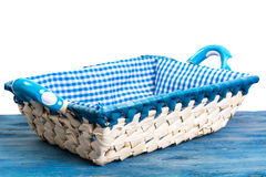 White wicker basket of bread with checkered cloth on blue backgr Royalty Free Stock Photography