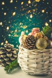White wicker basket with Christmas ornaments golden balls, pine cones, nuts, gift wrapping ribbon. Christmas greeting card Stock Photos