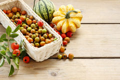 White wicker basket of rose hip fruits on wooden table Stock Photo