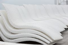 White wicker chaise lounges stacked in a pile and located around the pool, close-up, concept royalty free stock image