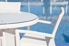 White wicker furniture by the pool. White wicker furniture sets by the pool, table and bronze chairs closeup view royalty free stock images