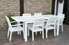 White wicker patio dining set. A picture of some high quality outdoor cane or rattan furniture, white resin wicker Patio dining set royalty free stock photos