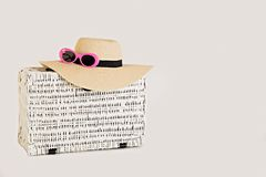 White wicker suitcase on a white background. Women`s accessories. A hat, sunglasses and shoes in pink color. Selective focus Stock Photography