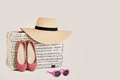 White wicker suitcase on a white background. Women`s accessories. A hat, sunglasses and shoes in pink color. Selective focus Stock Photos