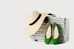 White wicker suitcase, a woman`s hat and green shoes. Stock Photos