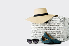 White wicker suitcase, women`s hat, glasses and blue shoes. Royalty Free Stock Photo