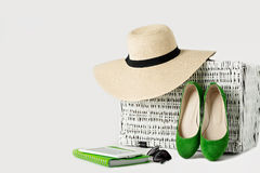 White wicker suitcase, womens hat, sunglasses, green shoes, e-bo Stock Images