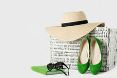 White wicker suitcase, womens hat, sunglasses, green shoes and n Stock Images