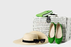 White wicker suitcase, womens hat, sunglasses, green shoes and n Royalty Free Stock Images