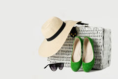 White wicker suitcase, womens hat, sunglasses and green shoes. Stock Photo