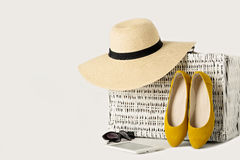 White wicker suitcase, womens hat, sunglasses, yellow shoes and Stock Image
