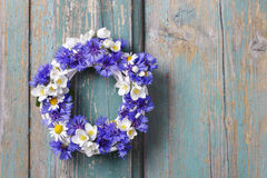 White wicker wreath decorated with cornflowers, chamomiles Stock Photos