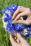 White wicker wreath decorated with cornflowers and chamomiles Royalty Free Stock Images