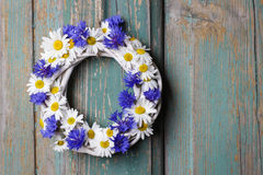 White wicker wreath decorated with cornflowers and chamomiles royalty free stock image