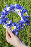 White wicker wreath decorated with cornflowers and chamomiles Stock Photos