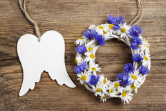 White wicker wreath decorated with cornflowers and chamomiles an Stock Images