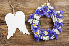 White wicker wreath decorated with flowers, and wooden angel win Royalty Free Stock Image