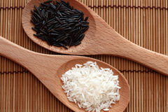 White and wild rice in a wooden spoons. White rice and wild rice in a wooden spoons on bamboo napkin. Close-up Stock Images
