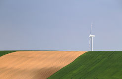 White wind power station in green field Royalty Free Stock Photos