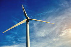 White wind turbine against blue cloudy sky at day, electric turbine with sky on background, alternative and renewable energy resou Royalty Free Stock Photo