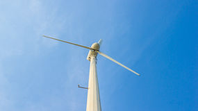 White wind turbine on blue sky Stock Photos