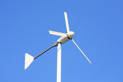 White wind turbine on clear blue sky Royalty Free Stock Images