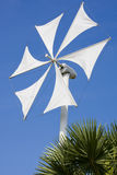White wind turbine generating electricity. On blue sky royalty free stock photography