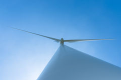 White wind turbine generating electricity on blue sky Royalty Free Stock Photo
