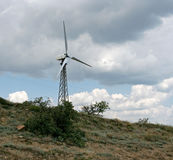 The white wind turbine on the mountain in the cloudy day. Royalty Free Stock Photo