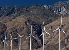 White Wind Turbines Against Colorful Mountain Back Stock Image