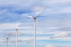 White wind turbines generating electricity alternative renewable energy from nature in wind power station Royalty Free Stock Photos